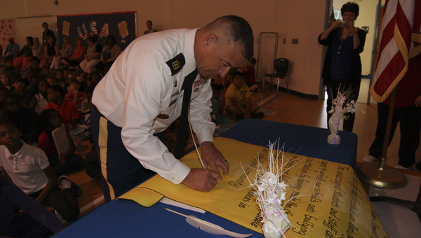 JOHN SMALL ELEMENTARY | CONTRIBUTED JOHN HANCOCK: Ret. 1st Sgt. Beattie with Washington High School JROTC signs John Small Elementary's Anti-bullying Constitution, which was also signed by all students, faculty and staff. The constitution is a pledge for the school to be bully-free.