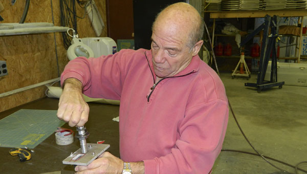 FILE PHOTO | DAILY NEWS DEDICATED: Tom Saccio, killed in a plane crash Thursday, works on avionics equipment in the hangar at his Maules Point home.