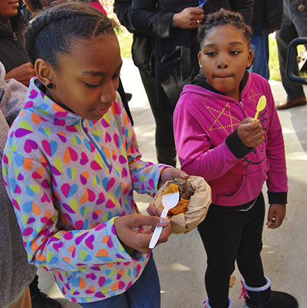 YUMMY:AniyahWeatherford(left), a fifth grader at S.W.SnowdenSchool, tastes portions of black-eyed peas and baked sweet potatoes while third graderDarnasiaTatum waits her turn.
